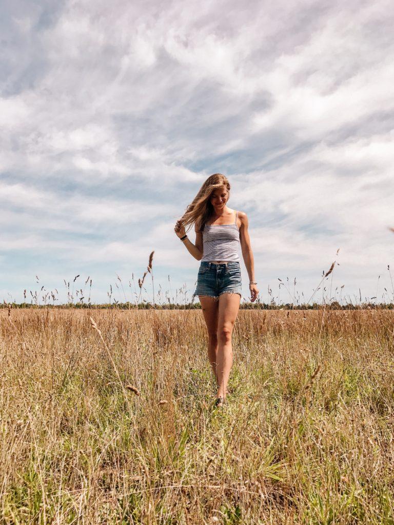blonde woman walking in a field